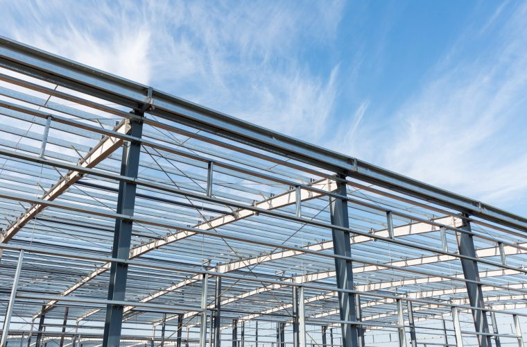 steel structure workshop is under construction against a blue sky