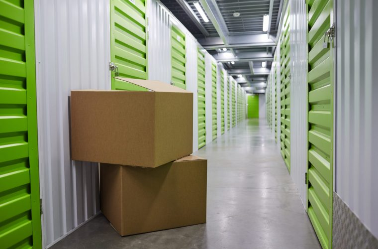 Image of stack of two big packages near the green storage boxes in storage room